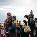 vluchtelingen onderweg met kinderen en bagage op rug