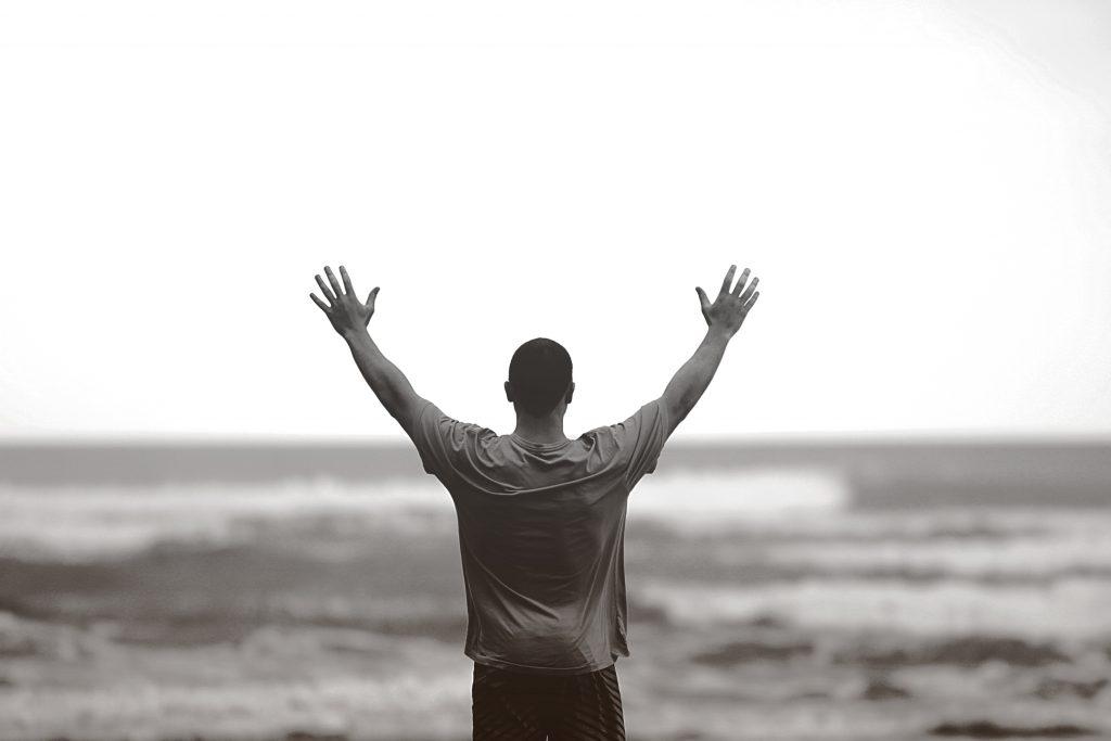 Man met geheven handen met gezicht naar oceaan