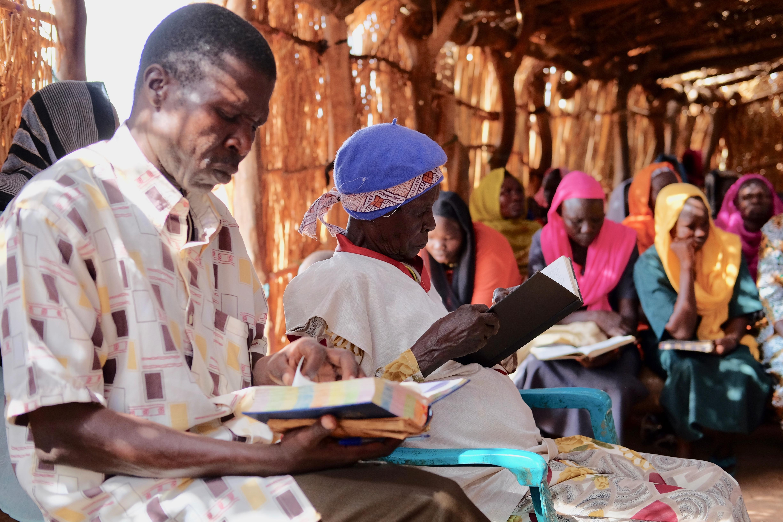 Familie die Bijbel bestudeert in hutje