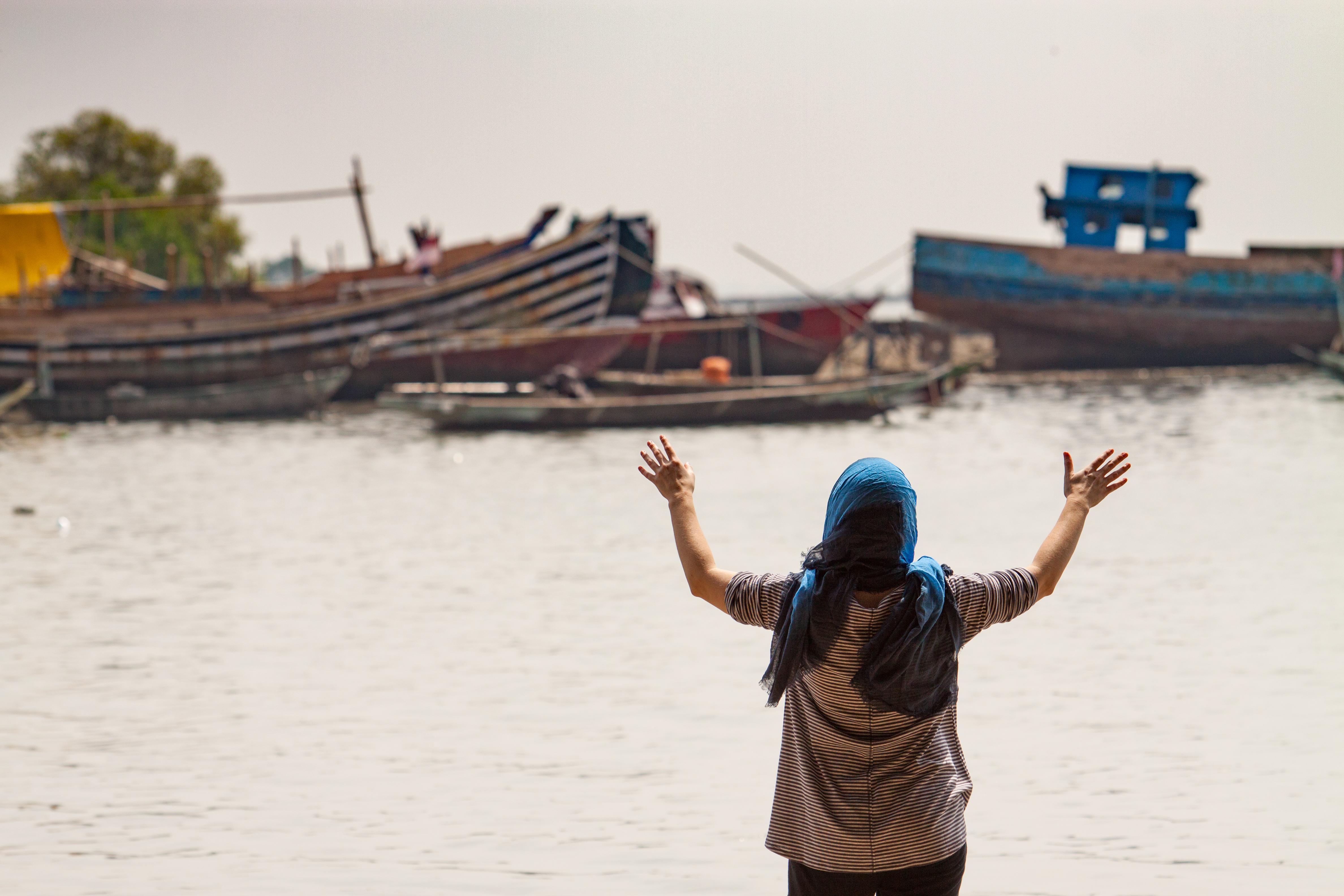 Indonesische vrouw met geheven handen voor rivier